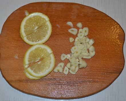 Нарезаем чеснок и лимон для рецепта как приготовить скумбрию в фольге